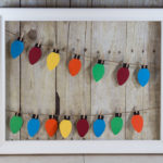 Learn how to make your own paper Christmas lights hanging display! | https://www.roseclearfield.com