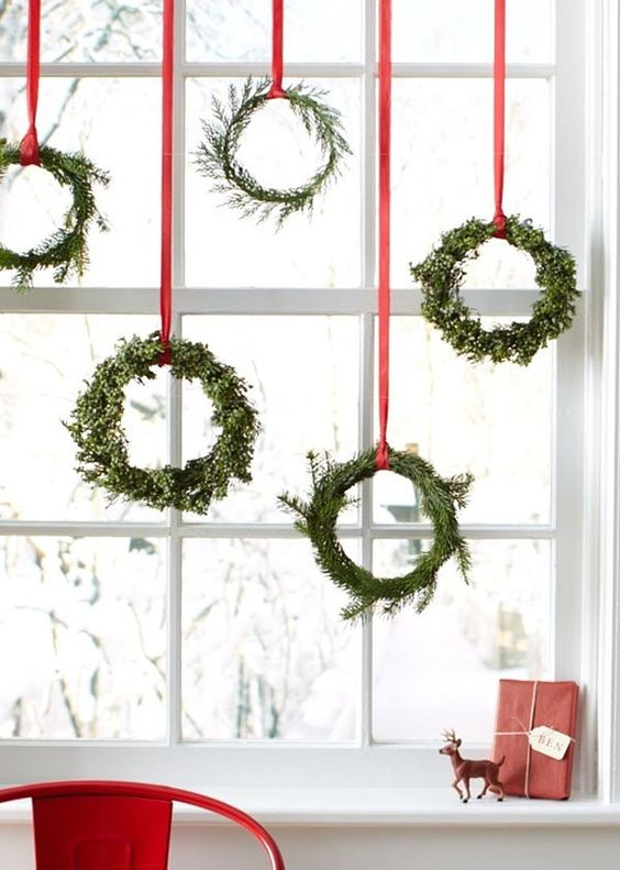 Christmas Decoration Inspiration - green wreaths hanging on red ribbons, so pretty!