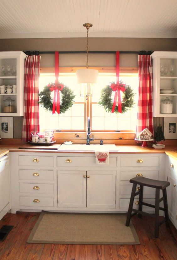 Simple, white kitchen with Christmas window decorations.