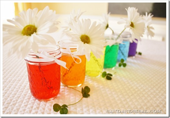 Rainbow Colored Water Mason Jar Centerpiece via Sand and Sisal | https://www.roseclearfield.com