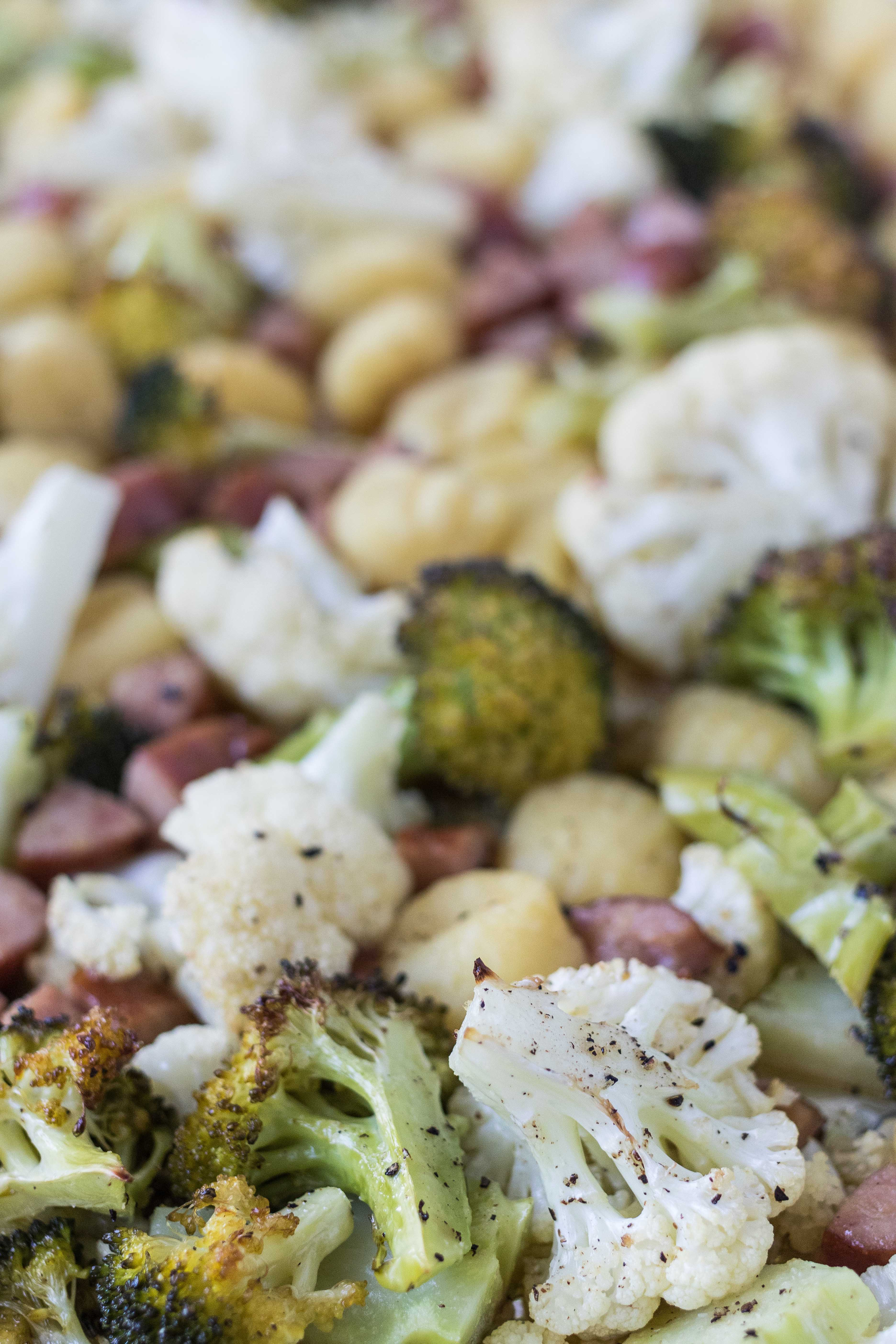 Roasted, crispy sheet pan gnocchi, chicken sausage, broccoli, and cauliflower. #sheetpandinner #healthyeating #chickensausage | https://www.roseclearfield.com