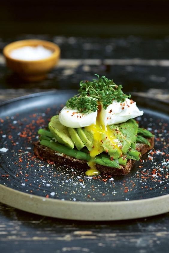 Avocado toast topped with asparagus and poached egg, via Tasting Table. Delicious and healthy! #avocadotoast #healthybreakfast #breakfastideas | https://www.roseclearfield.com