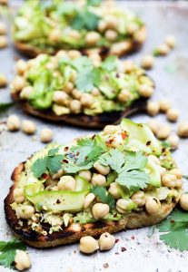 Avocado toast topped with spicy marinated chickpeas and zucchini. Perfect way to use up zucchini! via Floating Kitchen #healthyeating #avocadotoast #zucchinirecipe | https://www.roseclearfield.com