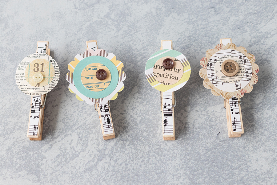 Sheet music clothespin magnets with homemade scrapbook embellishments. Such a pretty, simple touch to create one of a kind home decor! #DIY #sheetmusic #clothespins #scrapbookembellishments | https://www.roseclearfield.com