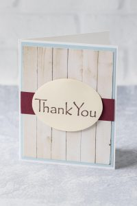 """Simple DIY thank you card with a faux wood background and deep red strip behind a mounted oval """"thank you."""" #thankyoucard #homemadecard #greetingcardinspiration 
