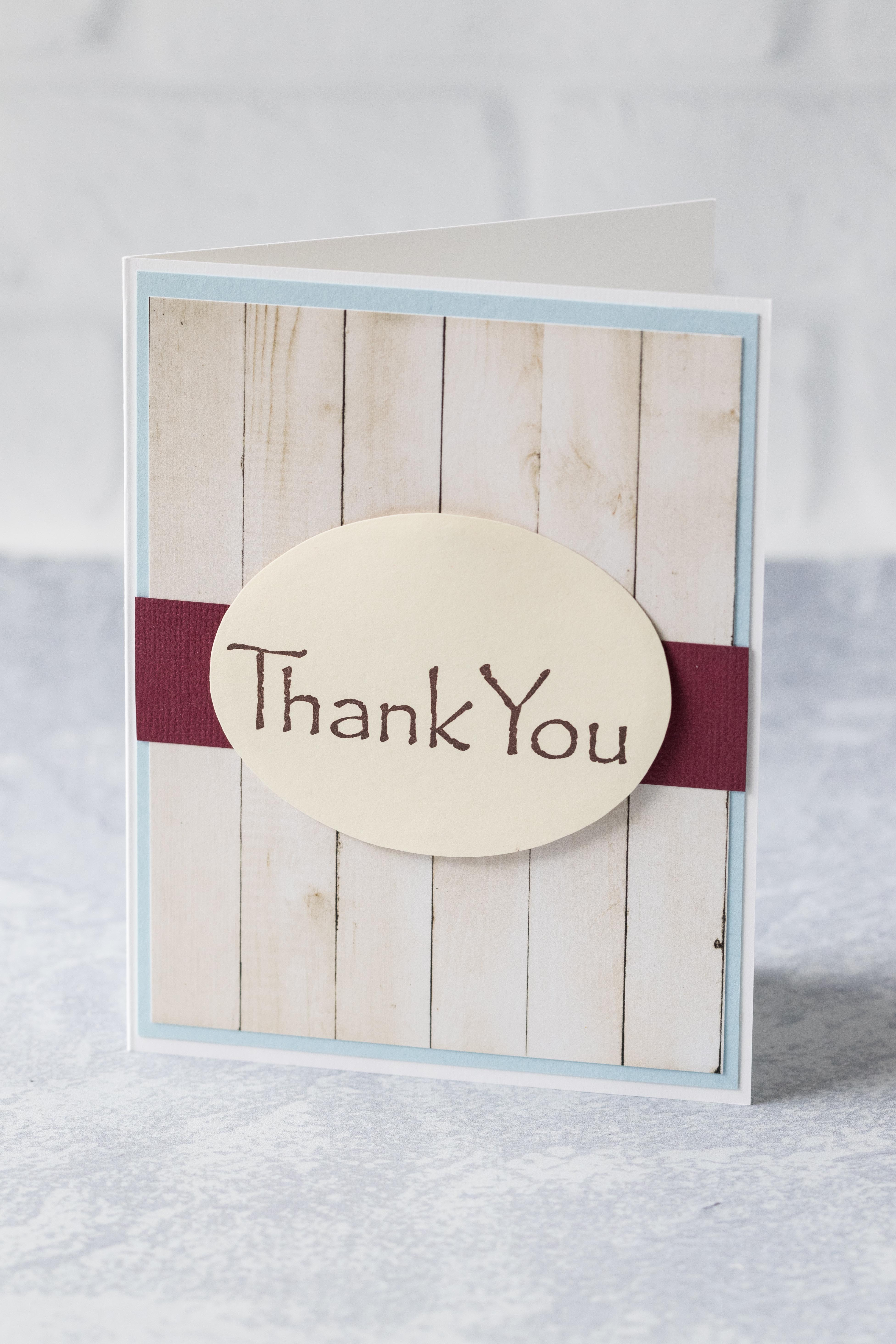 "Simple DIY thank you card with a faux wood background and deep red strip behind a mounted oval ""thank you."" #thankyoucard #homemadecard #greetingcardinspiration 