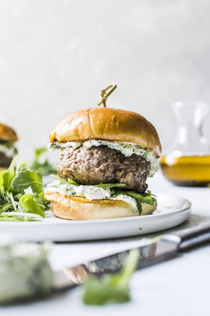 Lamb burgers with pesto whipped feta. Sure to impress summer guests during your next back yard barbecue! via The Almond Eater #lambburgers #whippedfeta #grilling | https://www.roseclearfield.com
